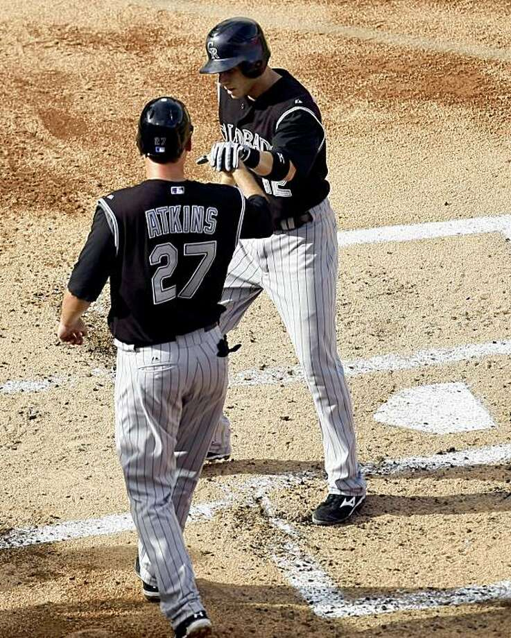 Colorado Rockies' Garrett Atkins (27) and Clint Barmes (12) celebrate Barmes' two-run home run in the second inning of Game 2 of a baseball doubleheader against the Florida Marlins on Sunday, Aug. 16, 2009, in Miami. (AP Photo/J Pat Carter) Photo: J Pat Carter, AP