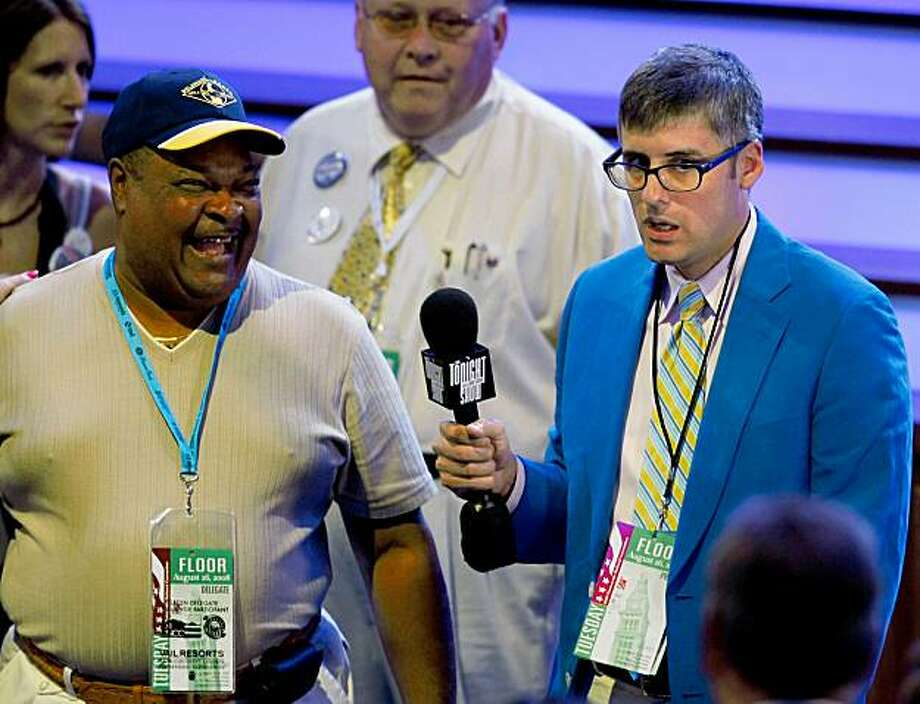 """DENVER - AUGUST 26:  """"The Daily Show's""""  Mo Rocca interviews a convention goer during day two of the Democratic National Convention (DNC) at the Pepsi Center August 26, 2008 in Denver, Colorado. U.S. Sen. Barack Obama (D-IL) will be officially be nominated as the Democratic candidate for U.S. president on the last day of the four-day convention. (Photo by Mark Wilson/Getty Images) Photo: Mark Wilson, Getty Images"""