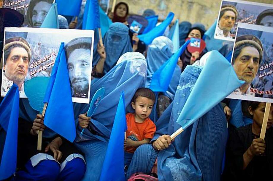 KABUL, AFGHANISTAN -AUGUST 17 :  Women with their babies hold posters of Presidential hopeful Abdullah Abdullah during a rally on the last day of campaigning on August 17, 2009 in Kabul, Afghanistan. There are three days to go before millions of Afghans go to the polls in the country's second democratic presidential election on August 20, which is overshadowed by Taliban threats. The incumbent President Karzai is considered to be the frontrunner despite claims of corruption and what many consider an ineffectual government.  (Photo by Daniel Berehulak/Getty Images) Photo: Daniel Berehulak, Getty Images