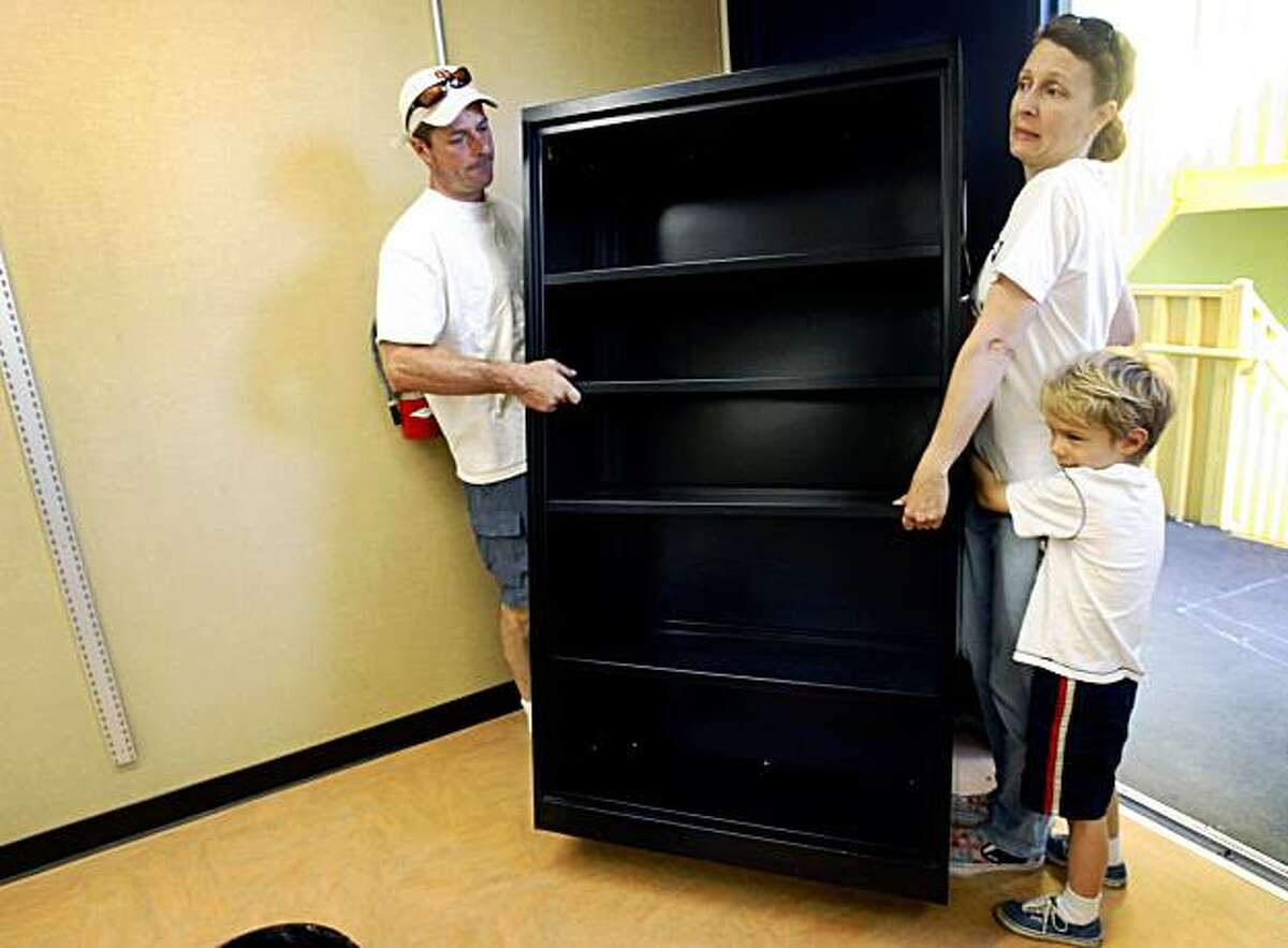 Steven Enfield (left) moves a bookcase with his wife Diana Bowen and their son Henry, an incoming Kindergartner, at Daniel Webster Elementary School in San Francisco, Calif., on Saturday, Aug. 15, 2009 where parents and other volunteers cleaned up and painted classrooms for the new school year.