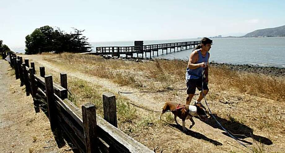 A man walks a dog at the Candlestick Point Recreation Area on August 14, 2009 in San Francisco, Calif. The state park is on a list of parks that may be vulnerable to closure due to state budget cuts. Photo: Lance Iversen, The Chronicle