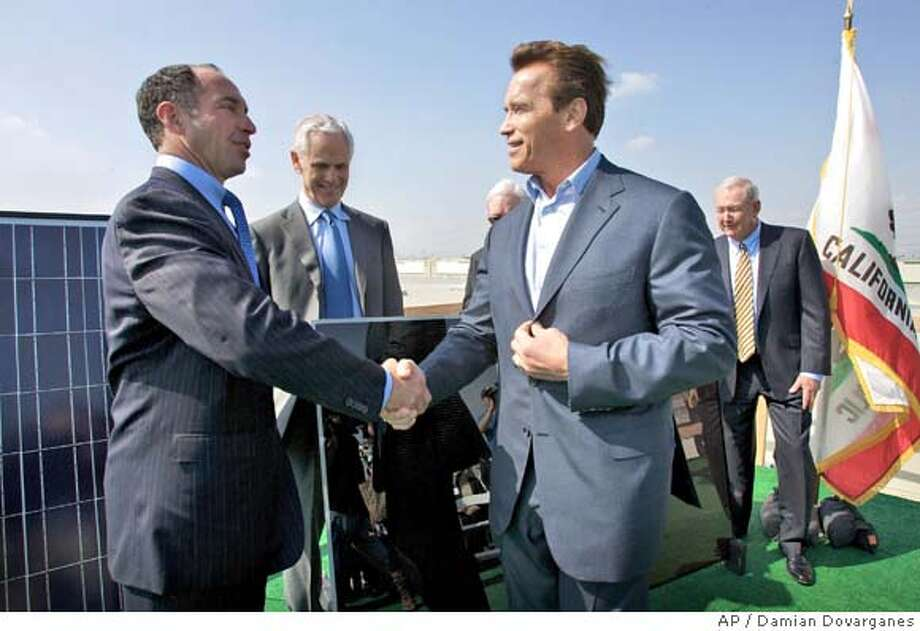 Jeffrey Schwartz, ProLogis chairman and CEO, far left, shakes hands with California Gov. Arnold Schwarzenegger, next to John Bryson, Edison International president and CEO , second from left, and John Fielder, Southern California Edison (SCE) president, far right, after announcing at a news conference in Fontana, Calif. Thursday, march 27, 2008, that SCE will build the nations largest solar energy installation, a project that will place 250 megawatts of advanced photovoltaic generating technology on 65 million square feet of roofs of Southern California commercial buildings, enough power to serve approximately 162,000 homes. (AP Photo/Damian Dovarganes) Photo: Damian Dovarganes