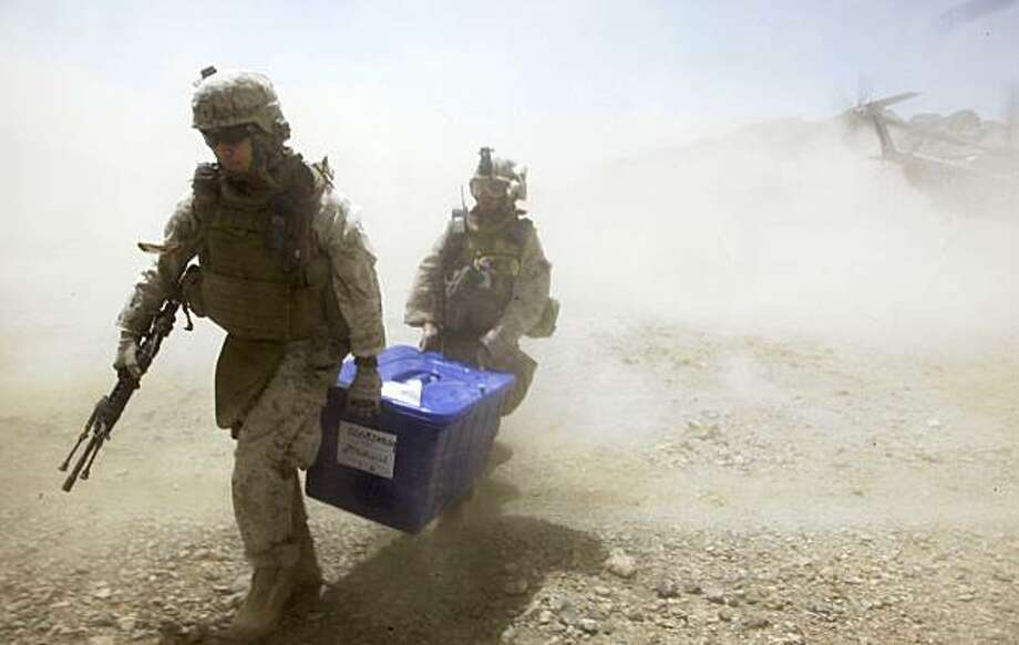 U.S. Marine Sgt. Raymond Shinahra, left, of Guam, and Navy Corpsman Michael Cannova, both attached to Golf Company, 2nd Battalion, 3rd Regiment, 2nd MEB, 3rd MEF, carry a box full of presidential ballots delivered by Marine helicopters from election headquarters in Lashkar Gah to election officials in Dahaneh Thursday, Aug. 20, 2009,  in the Helmand Province of Afghanistan. Officials in the village had discovered early in the morning that they were lacking any presidential ballots and could not open the voting process without them. (AP Photo/Julie Jacobson) Photo: Julie Jacobson, Associated Press