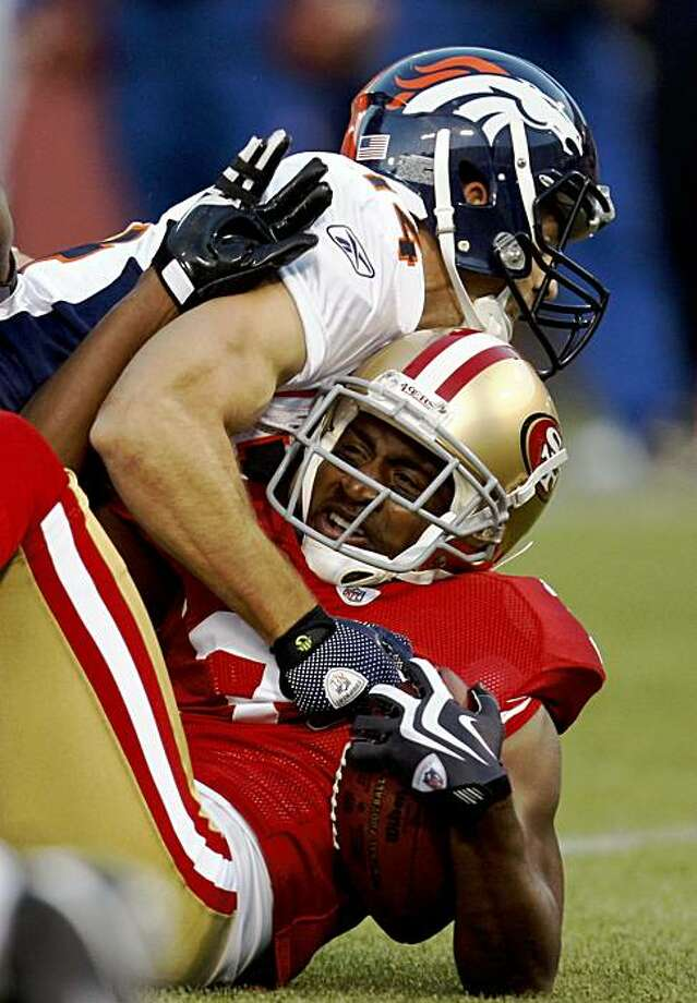San Frtancisco's Dre' Bly is brought down by Denver's Brandon Stockley after an interception in the second quarter of the San Francisco 49ers vs. Denver Broncos pre-season football game at Candlestick Park in San Francisco, Calif., on Friday, Aug. 14, 2009. Photo: Paul Chinn, The Chronicle