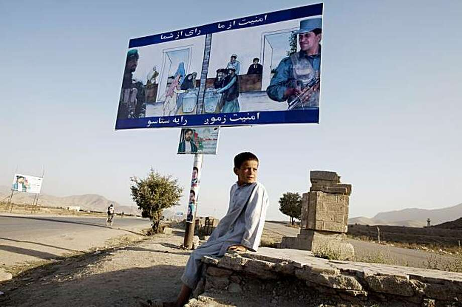 KABUL, AFGHANISTAN - AUGUST 13:  A boy sits by an election poster trying to get people to come out and vote  August 13, 2009 in Kabul, Afghanistan. The incumbent president Karzai is considered to be the frontrunner despite claims of corruption and what many consider an ineffectual government. Afghanistan's second presidential elections are to be held on August 20. Kabul August 12, 2009 in Afghanistan.  (Photo by Paula Bronstein/Getty Images) Photo: Paula Bronstein, Getty Images
