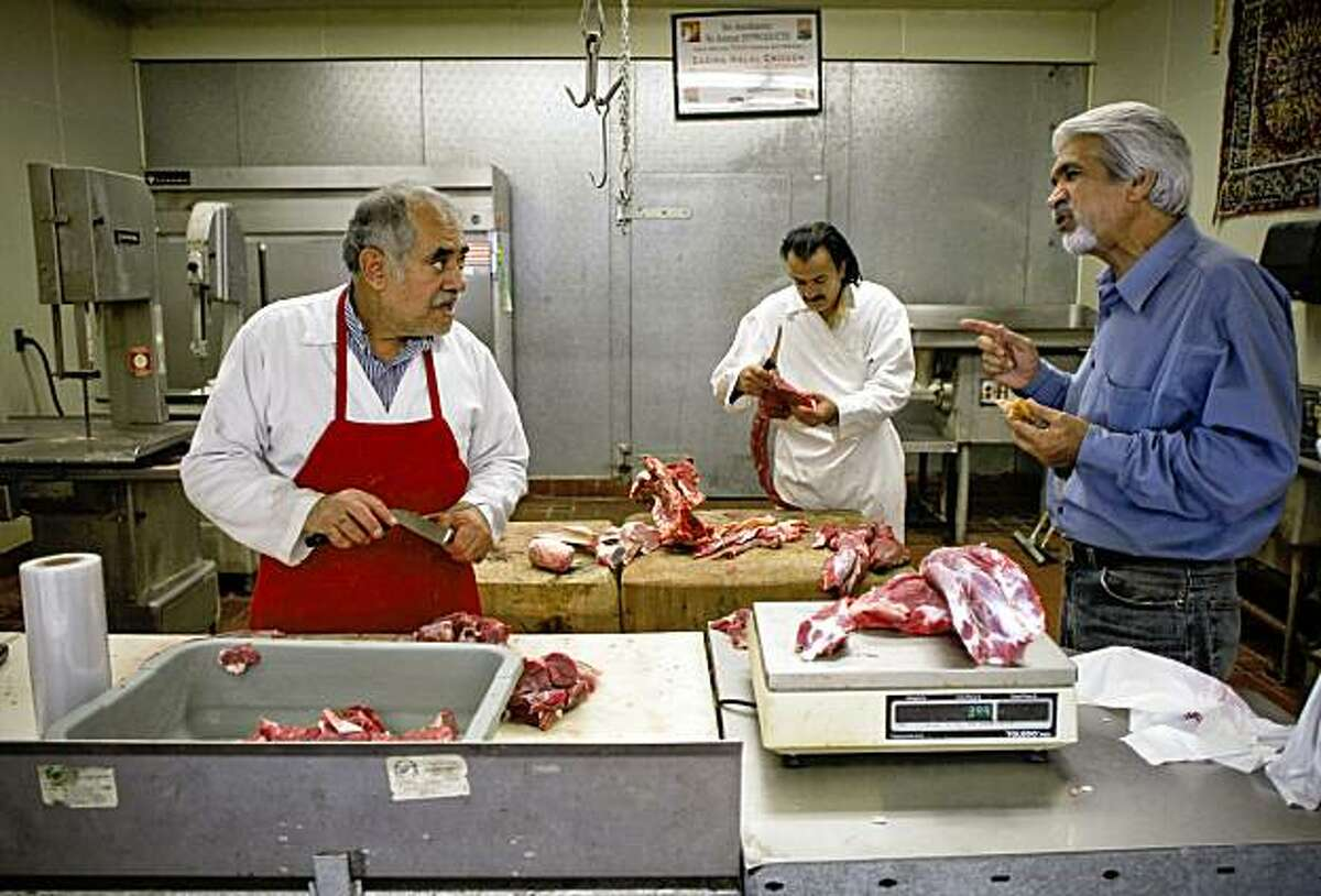 Butchers Abdul Halim, (left) and Homayn Hasson working at the Maiwand Market talk with Mohammad Bashizadah in the center of the Afghan community in Fremont, Calif., on Thursday August 20, 2009. Local Afghans in the Fremont community should find out on Saturday the results of Thursday's Presidential election.