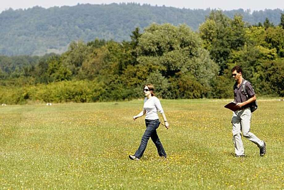 In this picture taken Tuesday, Aug. 18, 2009, Jan Souman, right, scientist at the Max Planck Institute in Tuebingen, Germany, walks behind his workmate Loes van Dam during a test run for his studies on an airfield near Tuebingen, Germany. Souman researches the phenomenon, that blindfolded people are not able to walk straight on but that they walk in a circle.  (AP Photo/Thomas Kienzle) Photo: Thomas Kienzle, AP