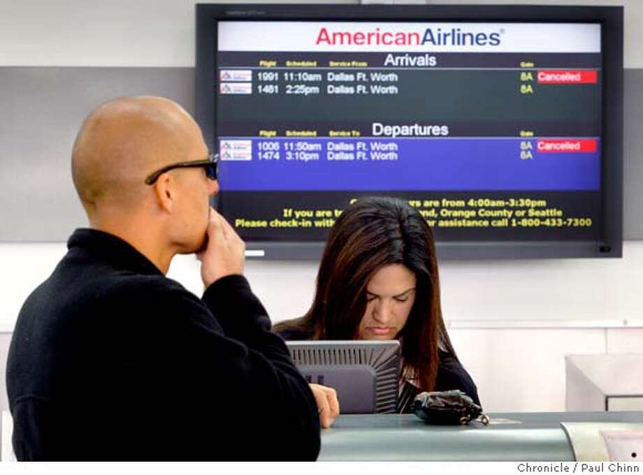 Albert Lopez, left, who was travelling with his family on American Airlines flight 1006, is assisted by ticketing agent Suzanne Bouldt at Oakland International Airport on Thursday, March 27, 2008. Lopez's flight, bound for Dallas-Fort Worth, was one of dozens grounded by the FAA so the plane's wiring can be inspected. He and his family were rebooked onto another airlines.  Photo by Paul Chinn / San Francisco Chronicle Photo: Paul Chinn