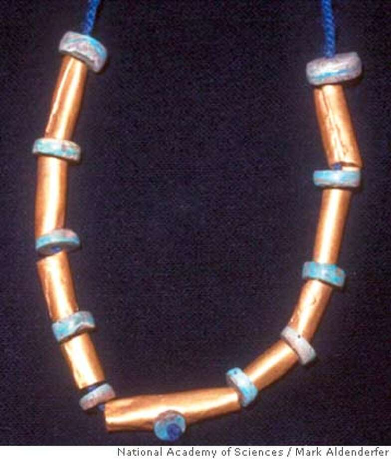 ** EMBARGOED UNTIL 5 P.M., MONDAY, MARCH, 31 2008 ** This undated handout photo provided by the Proceedings of the National Academy of Sciences shows a reconstruction the gold and turquoise beads as a necklace. The central gold bead has a turquoise bead attached through a perforation in its center. The earliest known gold jewelry made in the Americas has been discovered in southern Peru. The gold and turquoise necklace, made nearly 4,000 years ago, was found in a burial site near Lake Titicaca, researchers report in Tuesday's issue of Proceedings of the National Academy of Sciences. (AP Photo/National Academy of Sciences, PNAS, Mark Aldenderfer) Photo: Mark Aldenderfer