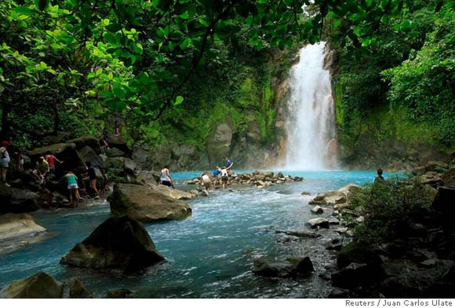 People swim in the Celeste river waterfall at Tenorio Volcano National Park in Upala March 18, 2008. The blue color of the lagoon, formed from chemical reactions of calcium carbonate and sulfur, is surrounded by amazing rainforest of 12,819 hectares of this park. The Celeste river carries its color for a distance of 36 km (22 miles). REUTERS/Juan Carlos Ulate (COSTA RICA)  Ran on: 03-27-2008  The Celeste River, at Tenorio Volcano National Park, is one of the many must-see spots for visitors to Costa Rica. Some tours take visitors on safaris through the country; others offer boat trips and hikes. Photo: JUAN CARLOS ULATE