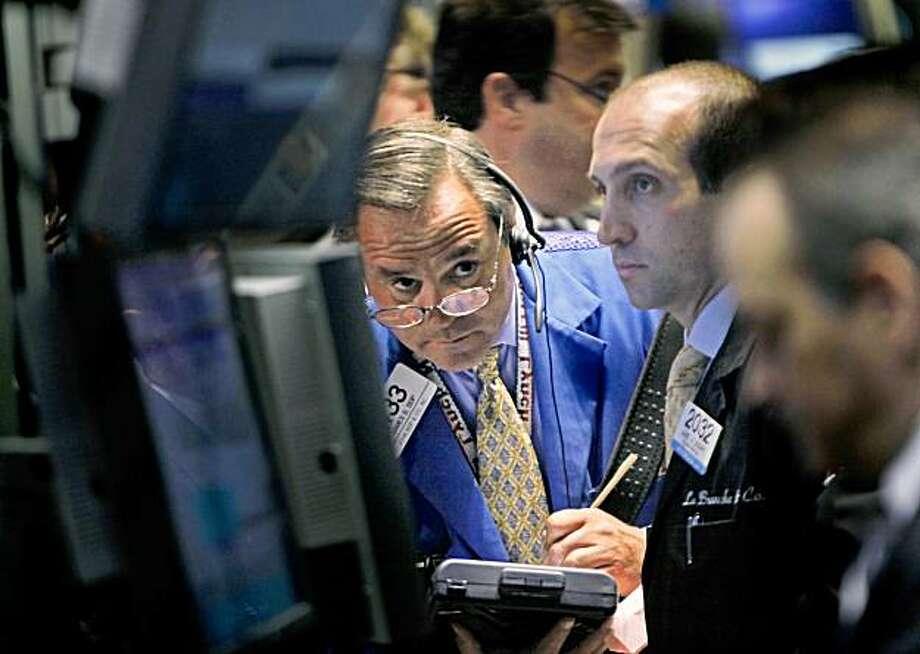 Traders work on the floor of the New York Stock Exchange, Monday, Aug. 17, 2009. (AP Photo/Seth Wenig) Photo: Seth Wenig, AP