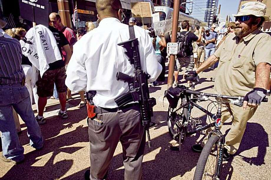 A man who supports the U.S. Constitution's Second Amendment right to keep and bear arms carries a military style AR-15 type rifle during a Obama opposition rally in Phoenix on Monday. Photo: Jack Kurtz, AP