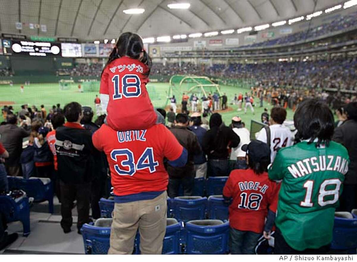 A girl wearing a Boston Red Sox pitcher Daisuke Matsuzaka T-shirt watches his team's practice session from the shoulders of an adult before the Major League Baseball regular season opener between the Red Sox and the Oakland Athletics at Tokyo Dome in Tokyo, Tuesday, March 25, 2008. (AP Photo/Shizuo Kambayashi)