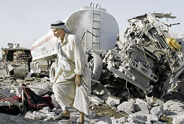 A man walks past a destroyed truck after a double truck bombing tore through a Shiite minority community near northern city of Mosul, 360 kilometers (225 miles) northwest of Baghdad, Iraq, Monday, Aug. 10, 2009. A series of blasts struck Baghdad Monday in a wave of predawn violence that killed at least 40 people, according to Iraqi officials. (AP Photo) Photo: STR, AP