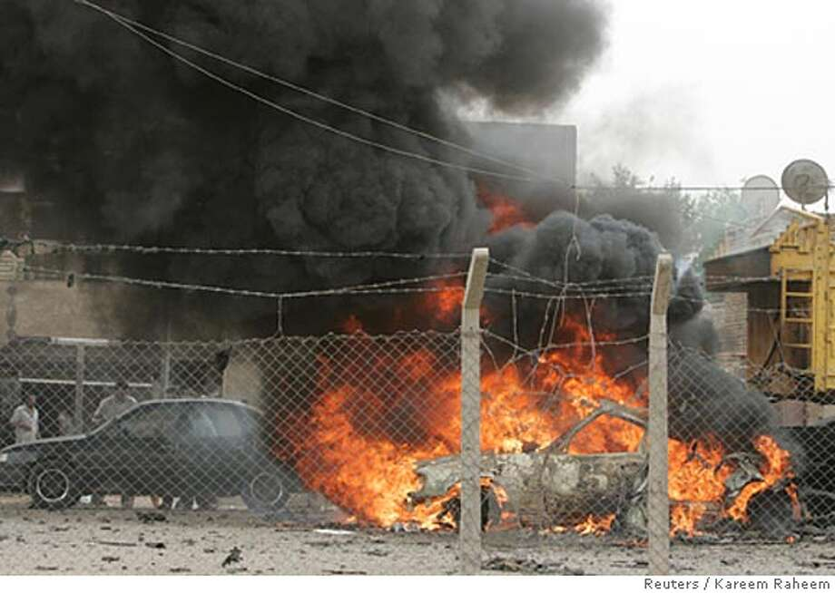 Vehicles burn after a U.S. air strike in a parking lot in Baghdad's Sadr City March 28, 2008. The attack killed four people and wounded three others, police said. REUTERS/Kareem Raheem (IRAQ) Photo: KAREEM RAHEEM