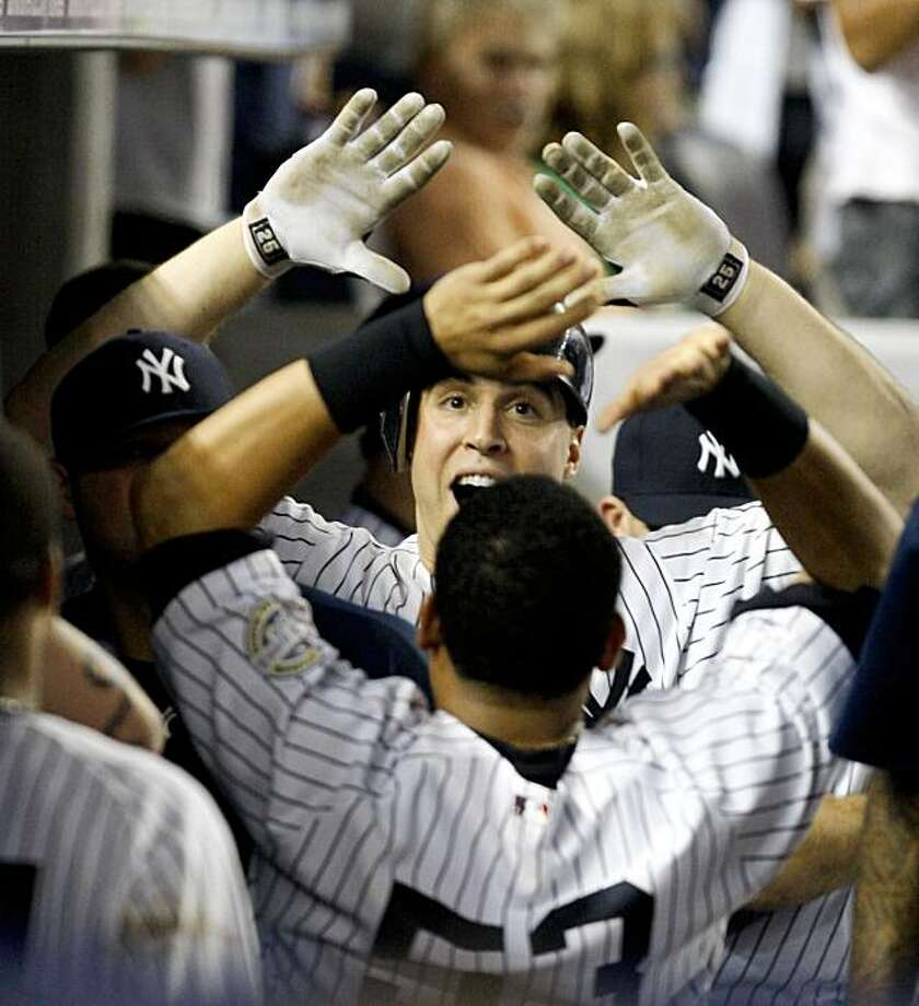 New York Yankees Mark Teixeira greets teammate Melky Cabrera in the dug out celebrating his two-run go-ahead home run in the bottom of the eighth inning in their baseball game against the Boston Red Sox at Yankee Stadium in New York, Sunday, Aug. 9, 2009. (AP Photo/Kathy Willens) Photo: Kathy Willens, AP