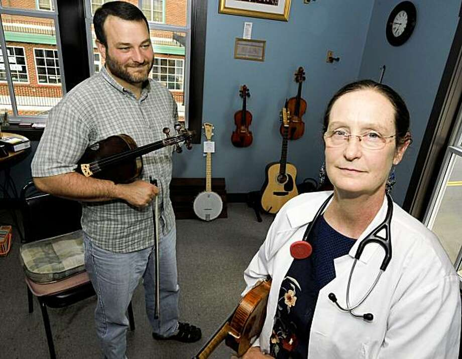 In this July 28, 2009 photo, osteopathic physician and bluegrass enthusiast Susan Osborne, right, and Floyd Music School director Mike Mitchell pose for a photo at the music school in Floyd, Va. Osborne bartered fiddle lessons with Mitchell and the fiddle she is holding with another patient, in exchange for her medical services. (AP Photo/Don Petersen) Photo: Don Petersen, AP