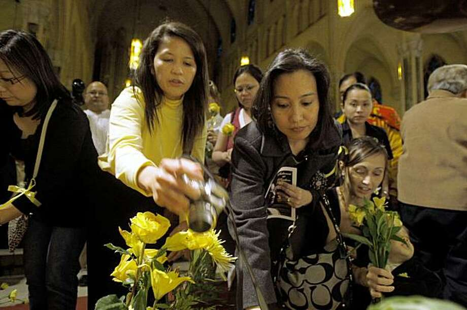 Mourners gather at St. Patrick Church to place yellow flowers at the altar in memory of former Philippine President Corazon Aquino in San Francisco Calif., on Thursday, August 6, 2009.  Yellow is the color Cory Aquino is associated with representing freedom. Photo: Liz Hafalia, The Chronicle