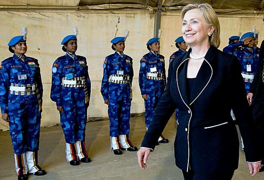 US Secretary of State Hillary Clinton reviews an honour guard by UN Indian policewomen during a welcoming ceremony on August 13, 2009 at Robert international airport near Monrovia. US Secretary of State Hillary Clinton praised Liberian President Ellen Johnson Sirleaf's post-war transformation of Liberia, dismissing a controversy over her alleged links to a warlord.    AFP PHOTO/ GLENNA GORDON/ POOL (Photo credit should read GLENNA GORDON/AFP/Getty Images) Photo: Glenna Gordon, AFP/Getty Images