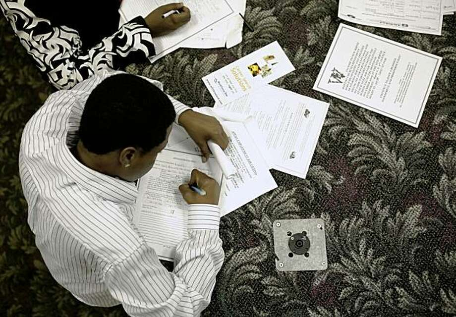 Aviander Fussell, 22, fills out job applications at a job fair at New Birth Enterprise in Miami, Thursday Aug. 13, 2009. The Labor Department said initial claims increased to a seasonally adjusted 558,000, from 554,000 the previous week. (AP Photo/Lynne Sladky) Photo: Lynne Sladky, AP