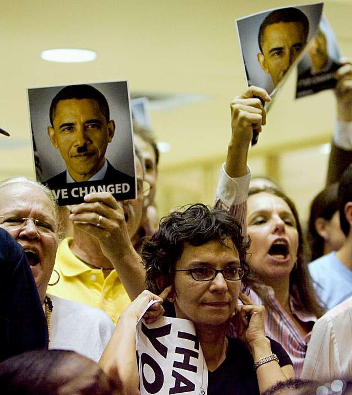 Maite Leal, center, plugs her ears as others shout during a town hall style meeting on health care reform at the Northeast Multi-Service Center in Houston, Wednesday, Aug. 12, 2009. (AP Photo/Houston Chronicle, Billy Smith II)