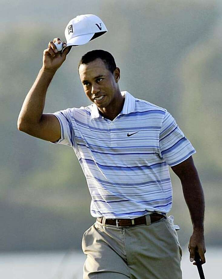 Tiger Woods tips his cap to the gallery after sinking a birdie putt on the 16th green during the second round of the 91st PGA Championship at the Hazeltine National Golf Club in Chaska, Minn., Friday, Aug. 14, 2009. (AP Photo/Paul Sancya) Photo: Paul Sancya, AP