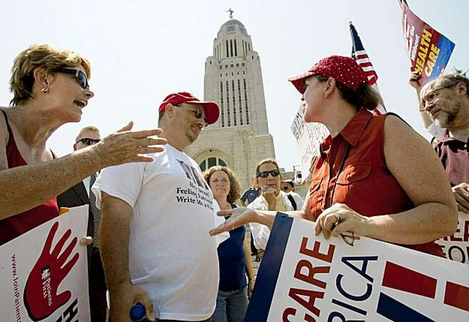 Demonstrators for and against the Democratic-led push to overhaul the country's health-care system, argue in Lincoln, Neb., Monday, Aug. 3, 2009, following a rally organized by conservative political advocacy group Americans for Prosperity.(AP Photo/Nati Harnik) Photo: Nati Harnik, AP