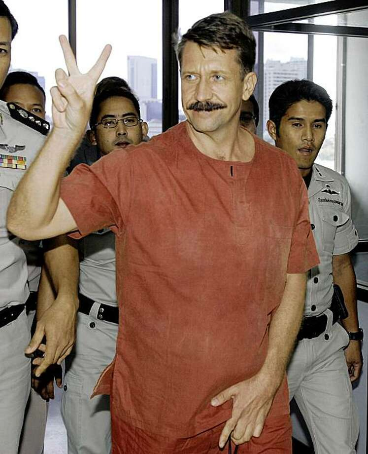 "Alleged Russian arms dealer Viktor Bout gestures while exiting a criminal court room in Bangkok, Thailand Tuesday, Aug. 11, 2009. A Thai court has rejected a U.S. request to extradite Bout dubbed the ""Merchant of Death"" to face terrorism charges. (AP Photo/Apichart Weerawong) Photo: Apichart Weerawong, AP"