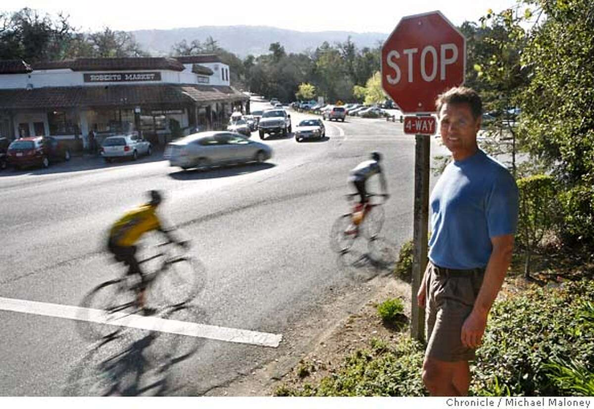 ###Live Caption:Marc Evans has his portrait taken on March 20, 2007 at a particularly dangerous intersection as bicyclists roll through a stop sign without stopping in Woodside, Calif. Evans, former triathlon coach for Kristy Gough, who was killed last weekend is now trying to raise awareness of the importance of cyclist safety and following traffic laws. Evans is planning to distribute bracelets that would signify a commitment to following traffic laws. Photo by Michael Maloney / San Francisco Chronicle###Caption History:Marc Evans has his portrait taken on March 20, 2007 at a particularly dangerous intersection as bicyclists roll through a stop sign without stopping in Woodside, Calif. Evans, former triathlon coach for Kristy Gough, who was killed last weekend is now trying to raise awareness of the importance of cyclist safety and following traffic laws. Evans is planning to distribute bracelets that would signify a commitment to following traffic laws. Bicyclists were twice as likely as drivers to be