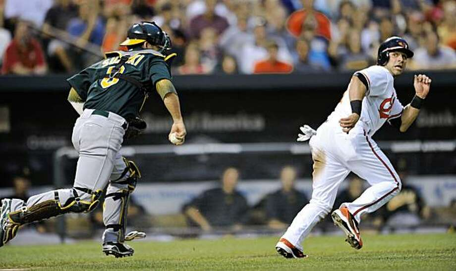 Baltimore Orioles Brian Roberts is caught in a run down as Oakland Athletics catcher Kurt Suzuki chases in the third inning of a baseball game Tuesday, Aug. 11, 2009 in Baltimore. Roberts was out on the play.(AP Photo/Gail Burton) Photo: Gail Burton, AP