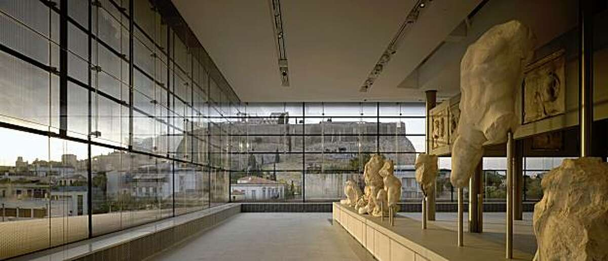 View of the Acropolis and Parthenon from the top-floor Parthenon Gallery of the New Acropolis Museum, Athens, Greece, designed by Bernard Tschumi. Foreground: sculptural fragments from the west pediment of the Parthenon