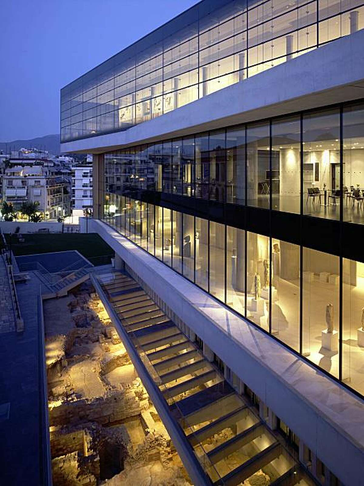 Exterior view of the of the New Acropolis Museum, Athens, Greece, designed by Bernard Tschumi, showing preserved 4th century A.D. ruins beneath the building.