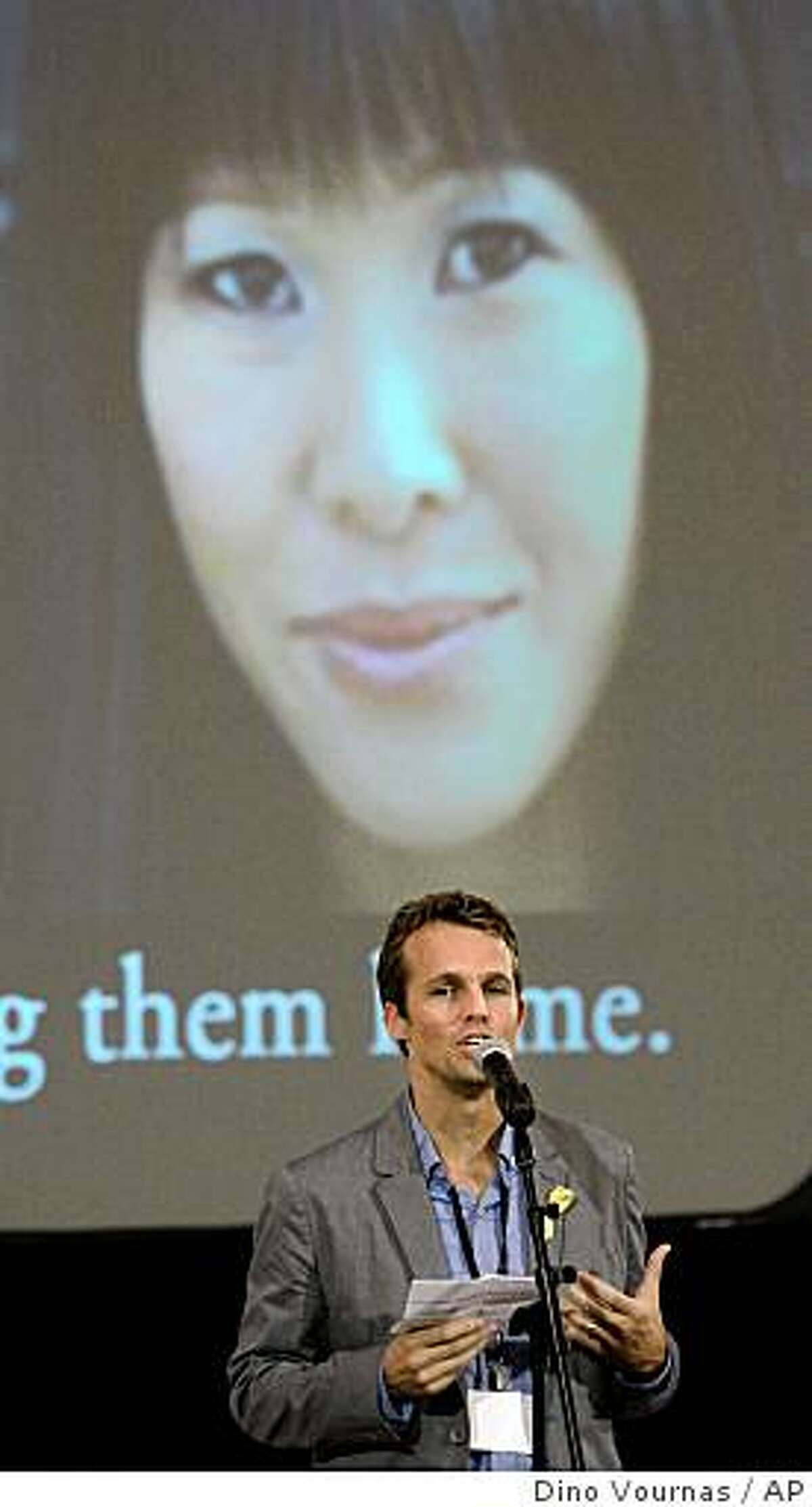 Iain Clayton, husband of Laura Ling (on screen), speaks to the crowd at the Academy of Art University during a vigil for the two journalists held by North Korea, Wednesday, June 24, 2009 in San Francisco. (AP Photo/Dino Vournas)