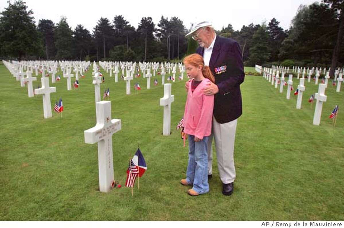 D Day survivor U.S. veteran Steve Kellman, 84, from Weston, Wisconsin, stands with his granddaughter Rita, 10, next to the grave of Lt. Jimmie W. Monteith Jr, who was leading his company when he was killed on June 6, 1944, at the Colleville sur Mer, American cemetery, Wednesday June 6, 2007, on the 63rd anniversary of the allied army landing in Normandy, France.(AP Photo/Remy de la Mauviniere) Ran on: 06-07-2007 Steve Kellman, 84, a D-Day survivor from Weston, Wis., shows his granddaughter Rita the grave of his company commander at the American cemetery at Colleville-sur-Mer, France.