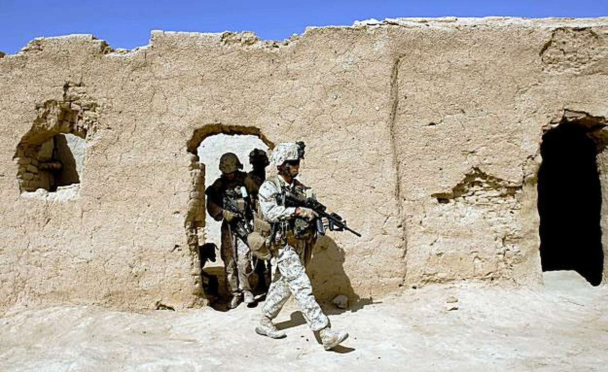 US Marines of 2nd Battalion 8 Marines of 2nd Marine Expeditionary Brigade help the Afghan National Army search compounds for insurgents in Gharmsir district in Helmand Province on July 27, 2009.. About 4,000 US Marines are battling insurgents in a massive offensive launched in the south early this month to clear Taliban militants out of strongholds ahead of presidential and provincial council elections scheduled for August 20. AFP PHOTO/ Manpreet ROMANA (Photo credit should read MANPREET ROMANA/AFP/Getty Images)