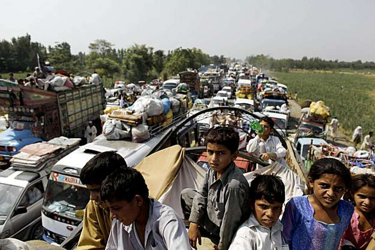 Refugees line up at a check point prior to going back to Swat Valley, in Shergarh, Pakistan, Friday, July 17, 2009. After weeks in sweltering camps, refugees from the Swat Valley began heading home Monday, the first day of the government's official repatriation program for those uprooted by fighting there. (AP Photo/Alexandre Meneghini)