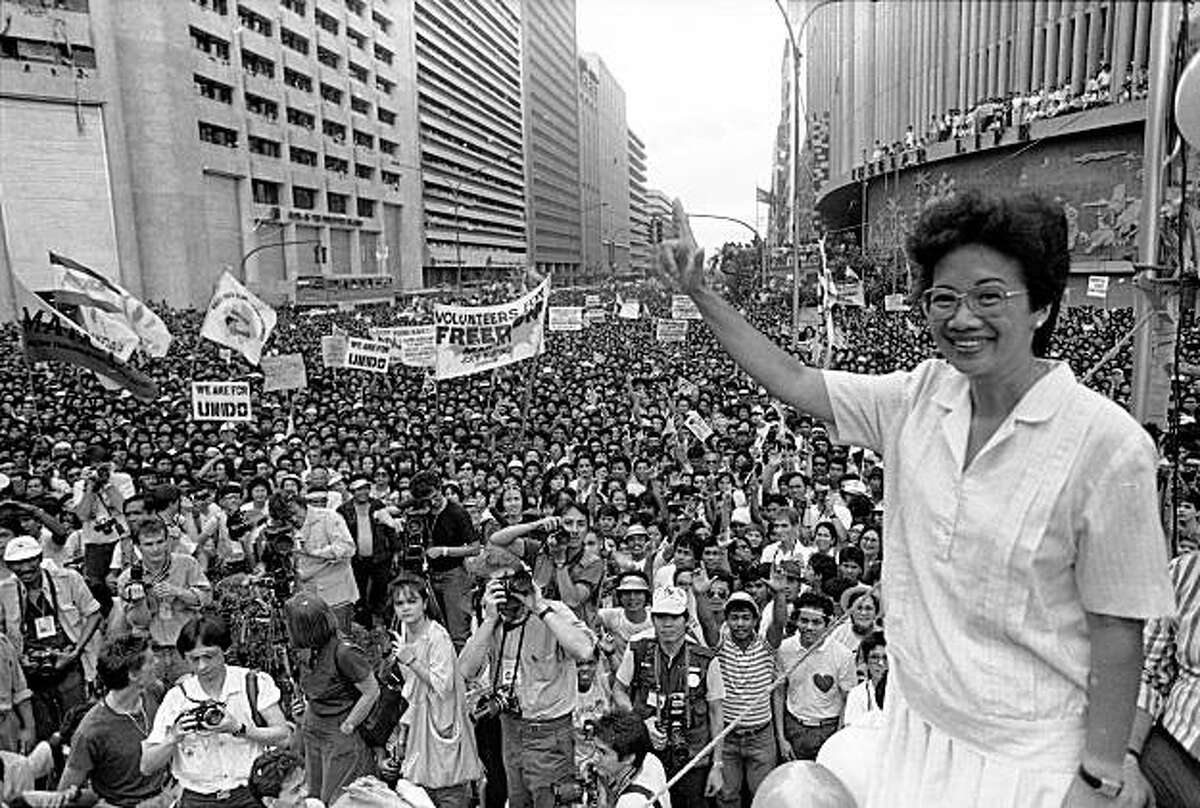 FILE - In this Jan. 27, 1986 file picture, opposition presidential candidate Corazon Aquino waves from the podium as thousands of supporters cheer during a campaign rally in downtown Manila. Aquino, who swept away a dictator and then sustained democracy by fighting off seven coup attempts in six years, died Friday, July 31, 2009. She was 76. (AP Photo/Val Rodriguez)