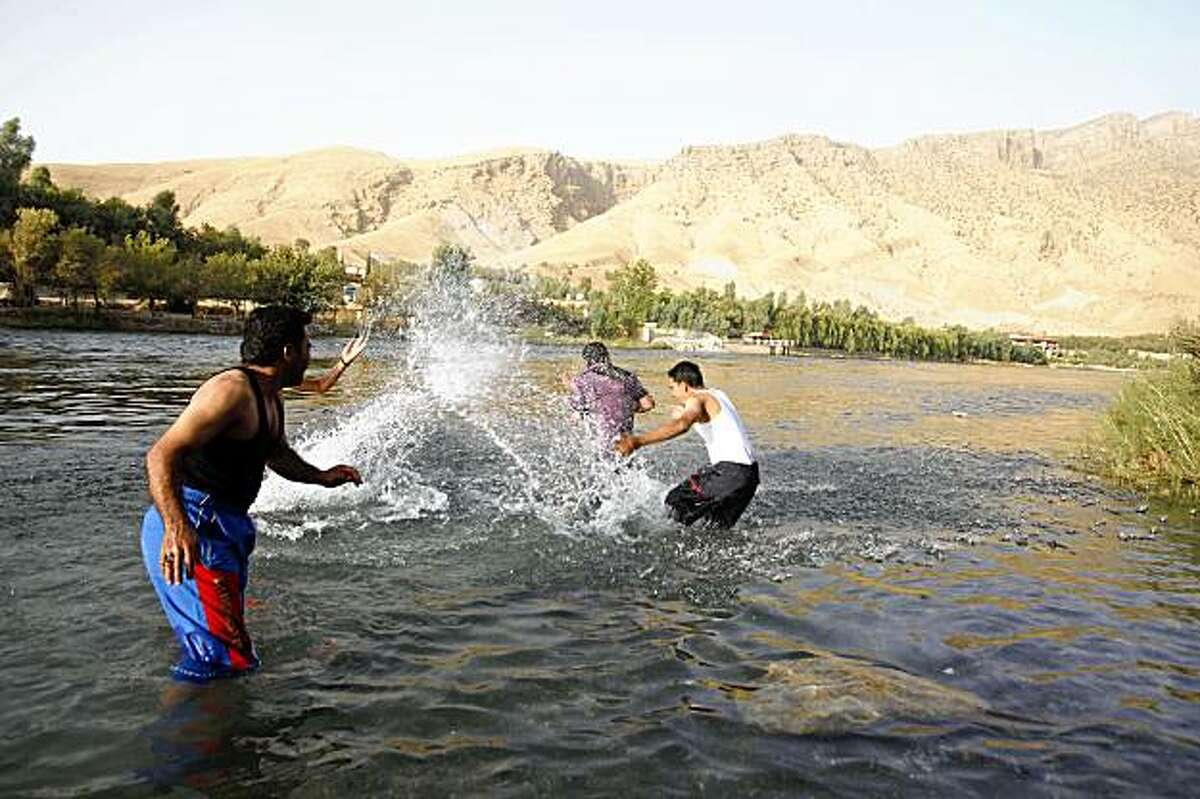 ** CORRECTS NAME OF RESORT ** Foreign and local tourists are seen at Dukan Resort, where three American hikers were last seen, near Sulaimaniyah, 260 kilometers (160 miles) northeast of Baghdad, Iraq, Monday, Aug. 3, 2009. Iranian authorities have given no word on three Americans detained after reportedly wandering across the border with Iraq last week during a hike in the Iraqi Kurdish region. (AP Photo/Hadi Mizban)