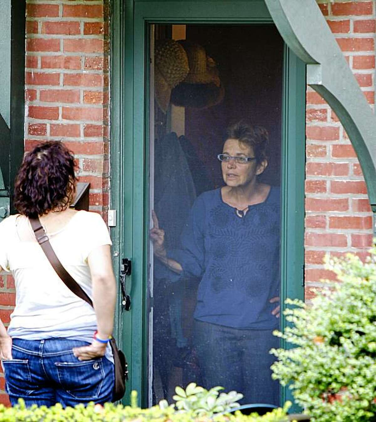 A member of the local news media, left, attempts to speak with family of missing American Joshua Fattal at his parents home in Elkins Park Pa., on Sunday Aug. 2, 2009. The subject inside the home offered no comment. (AP Photo/ Joseph Kaczmarek)
