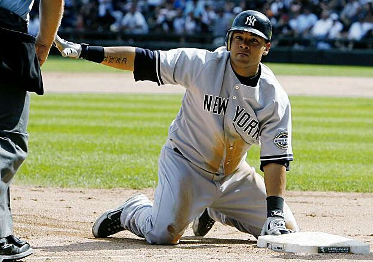 New York Yankees' Melky Cabrera slides safely into third base after hitting a triple against the Chicago White Sox during the ninth inning of a baseball game in Chicago, Sunday, Aug. 2, 2009. (AP Photo/Nam Y. Huh)