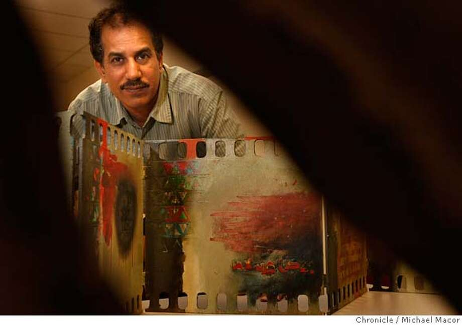 Accomplished abstract artist, Karim Alwali,42, fled Iraq in 2007, he displays a piece of his art, on Mar. 12, 2008, depicts the destruction along Almutanabi St. in Baghdad, Iraq from the invasion by coalitions forces in 2003, Alwali near his home in San Jose, Calif. Photo by Michael Macor/ San Francisco Chronicle Ran on: 03-16-2008  Karim Alwali is using his unique painting skills to tell the powerful story of his war-torn country of Iraq while he is living in San Jose. Photo: Michael Macor