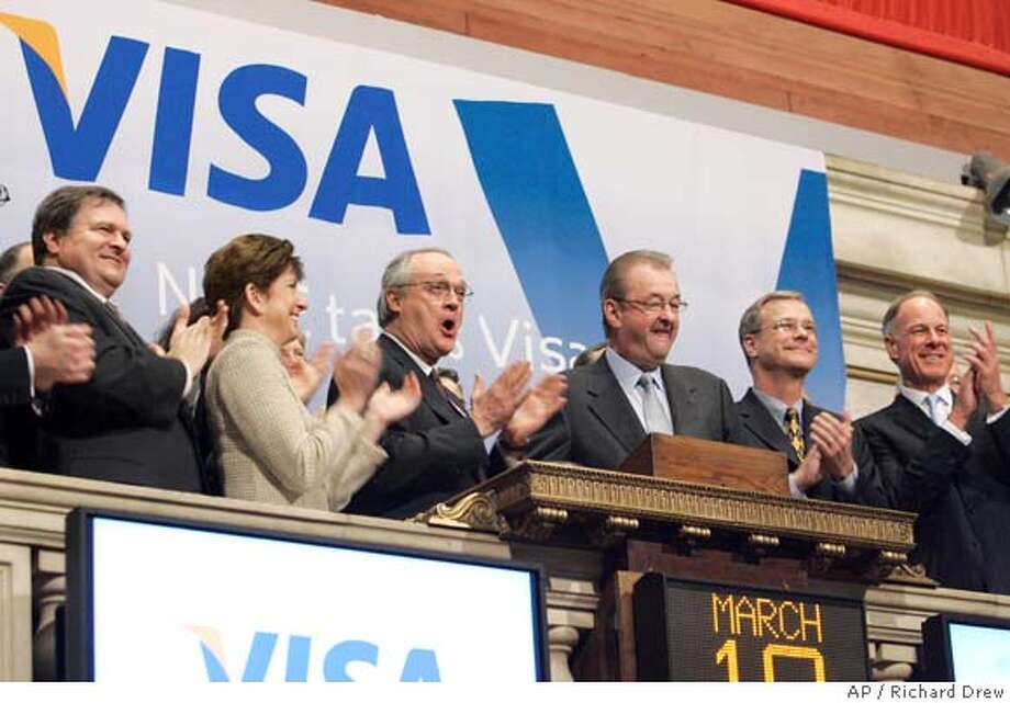 Visa Chairman and CEO Joseph Saunders, third from right, is applauded as he rings the New York Stock Exchange opening bell during his company's initial public offering, Wednesday March 19, 2008. Joining the celebration are NYSE Chairman Marshall Carter, third from left, Visa CFO Byron Pollitt, second from right, and Visa COO John Partridge, right. Overcoming the jitters that have battered many of the lenders that issue its cards, Visa Inc. sold 406 million shares at $44 apiece late Tuesday to raise nearly $18 billion and complete the most lucrative initial public offering in U.S. history. (AP Photo/Richard Drew) Photo: RICHARD DREW