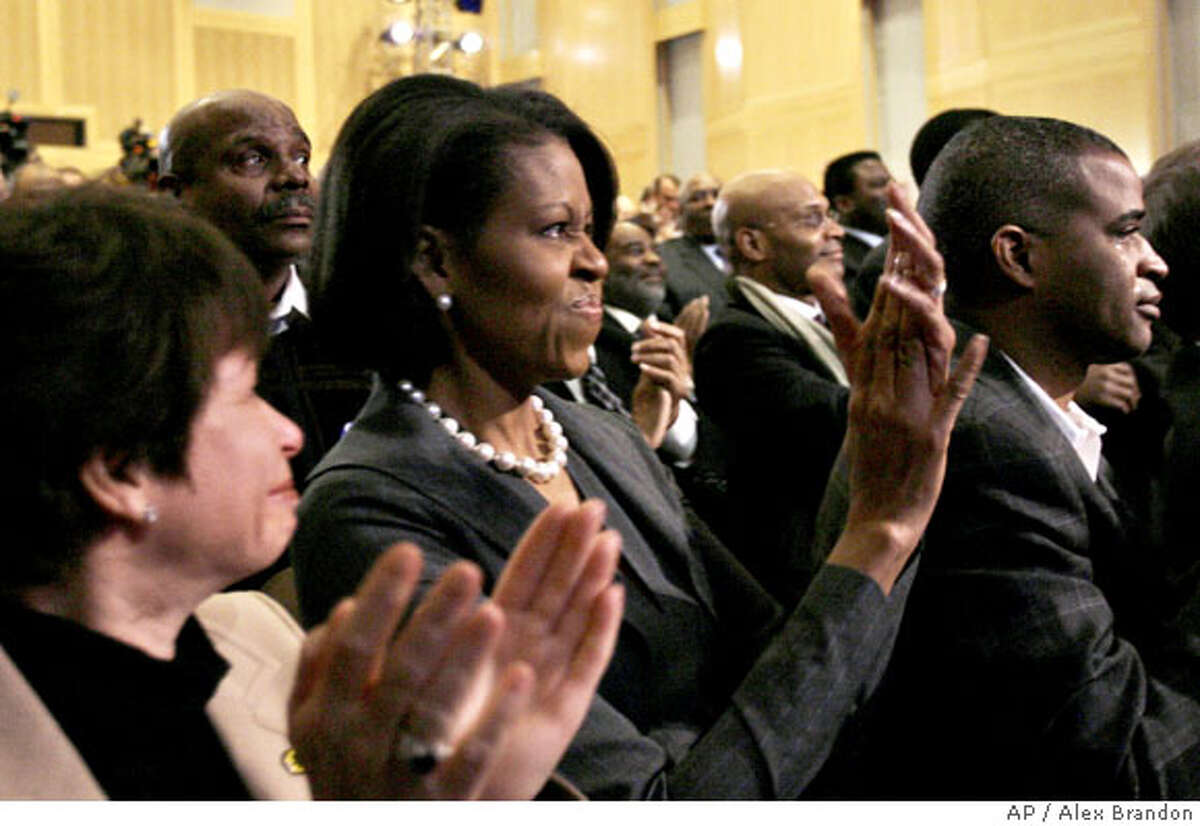 Michelle Obama, wife of Democratic presidential hopeful Sen. Barack Obama D-Ill., second from left, along with Valerie Jarrett, left, Marty Nesbitt, right, and others, applauds prior to her husband's speech about race, Tuesday, March 18, 2008, in Philadelphia. (AP Photo/Alex Brandon)