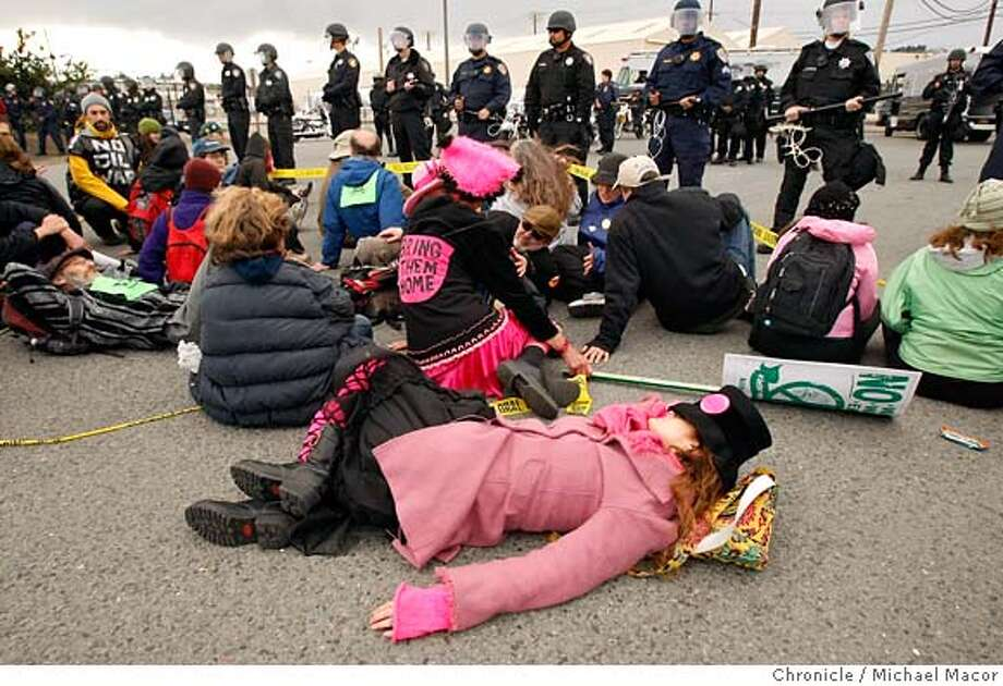 "###Live Caption:Pam Bennett, a member of Code Pink, joins several other protesters on the private property of the Chevron Oil Refinery in Richmond, Calif., on March 15, 2008, during a protest against the company's involvement in the production of Iraqi oil. Photo by Michael Macor/ San Francisco Chronicle###Caption History:Pam Bennett, takes a little rest while on the front lines, she is with the group Code Pink, out of San Francisco, she joins several other protesters as they move onto the private property of the Chevron Oil Refinery in Richnmond, Calif., on Mar. 15, 2008, as a protest against the company's involvement in the production of Iraqi oil. The Richmond Police department stands ready to keep the group back. Photo by Michael Macor/ San Francisco Chronicle###Notes:Day-long series of protests and attempted blockade of Chevron refinery Saturday, Mar. 15, because of the blood-soaked oil it imports from Iraq and because of proposed refinery upgrade that will allow it to process ""dirtier"" oil and thus allegedly poison###Special Instructions:Mandatory credit for Photographer and San Francisco Chronicle No sales/ Magazines Out Photo: Michael Macor"