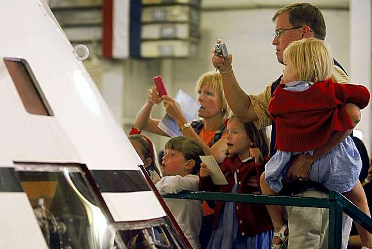 Space fans, including the Grifin and Saidy families, lined up to photograph a mock-up of the Apollo 11 command module before Buzz Aldrin's presentation at the USS Hornet aircraft carrier museum in Alameda, Calif., on Saturday, July 25, 2009. The Hornet picked up the three-man astronaut crew after splashing down in the Pacific completing its historic mission to the moon 40 year years ago.