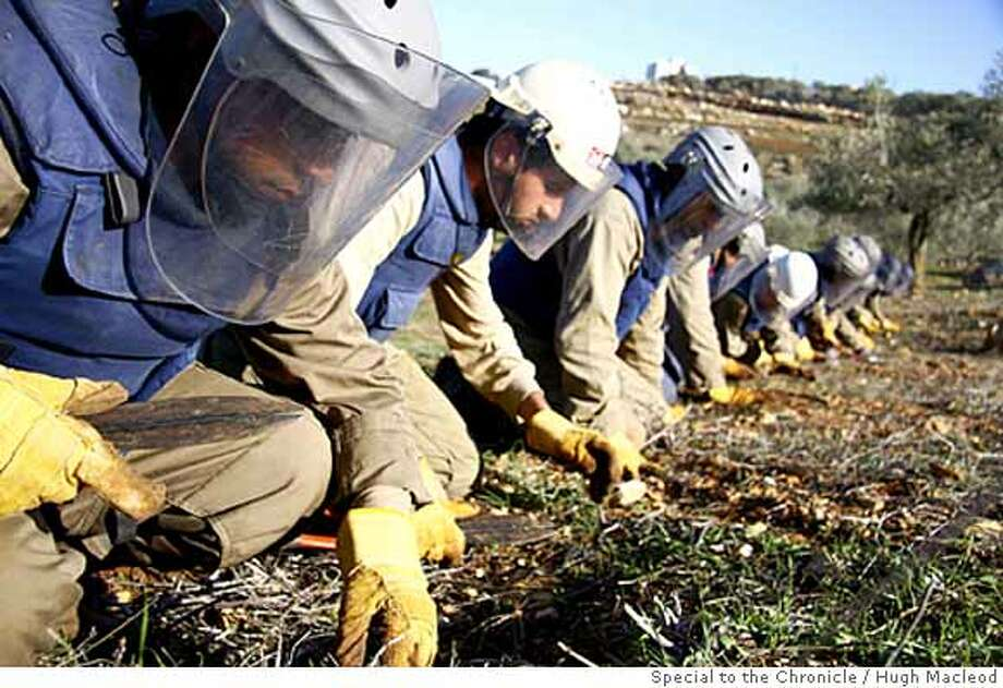 U.N. deminers scour farmland in the village of Zawtar West in southern Lebanon for Israeli-dropped cluster bombs in February, 2008. More than 100 nations are set to ratify a ban on the use of cluster bombs before the end of the year.  Photo by Hugh Macleod / Special to The Chronicle Photo: Hugh Macleod