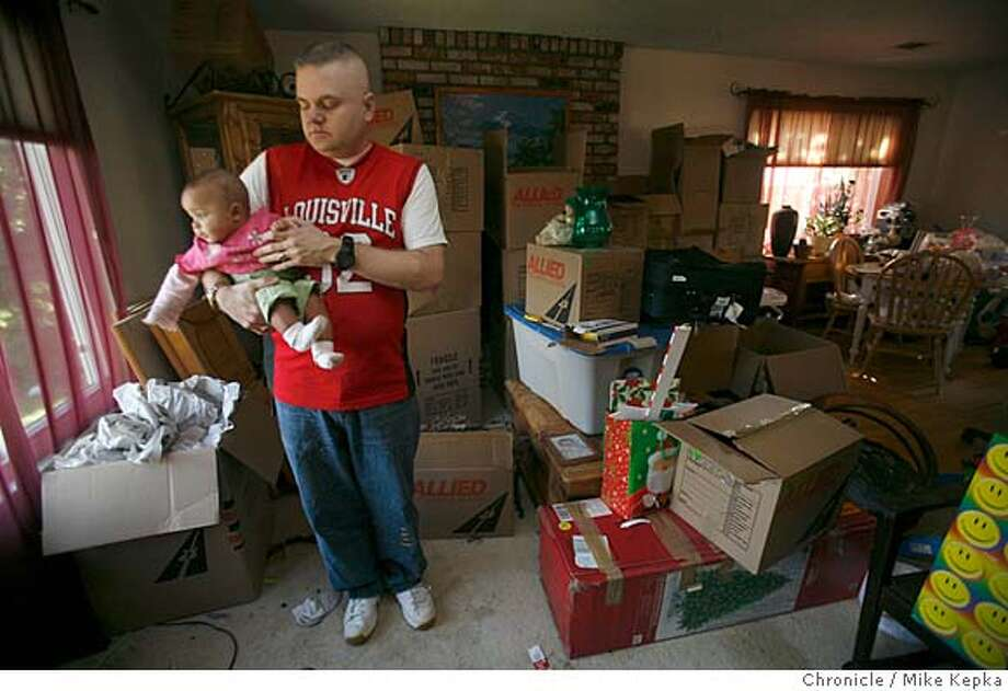 Standing is a living room full of packed boxes, Army Sgt. first class, Nicklaus Skaggs, his daughter, Madisyn Skaggs,6 months, is debating a voluntary foreclosure on his home of 3 years Vacaville, Calif., on Thursday, Mar. 13, 2008. The Skagg family bought their for home for $455,000. Now faced with rising mortgage payments, they figure their property is worth $160,000 less than they paid for it. As their other debts grow they are ready to walk away in order to save themselves from complete financial disaster.  Photo by Mike Kepka / San Francisco Chronicle Ran on: 03-16-2008  Nicklaus Skaggs holds his daughter Madisyn in the Vacaville home that his family is walking away from in a foreclosure.  Ran on: 03-16-2008  Nicklaus Skaggs holds his daughter Madisyn in the Vacaville home that his family is walking away from in a foreclosure. Photo: Mike Kepka