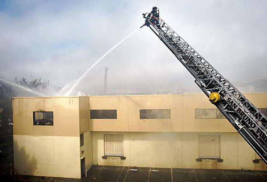 Ladder trucks helped firemen aim water on the roof of the packing plant Thursday morning. South San Francisco and nearby fire departments poured water on a four-alarm fire at a packing plant used by Columbus Salami Thursday July 23, 2009. Photo: Brant Ward, The Chronicle