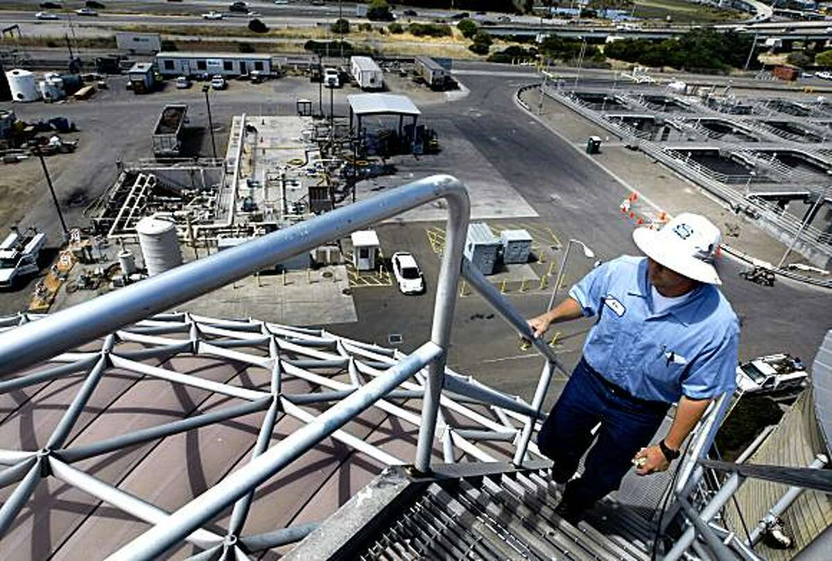 EBMUD plant operator Eric Fukuda climbs one of two anaerobic digester tanks used to make methane gas that powers the plant. Tuesday July 21, 2009