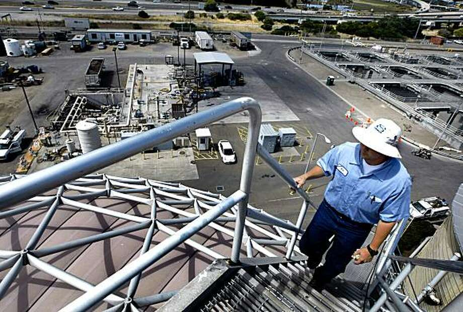 EBMUD plant operator Eric Fukuda climbs one of two anaerobic digester tanks used to make methane gas that powers the plant. Tuesday July 21, 2009 Photo: Lance Iversen, The Chronicle